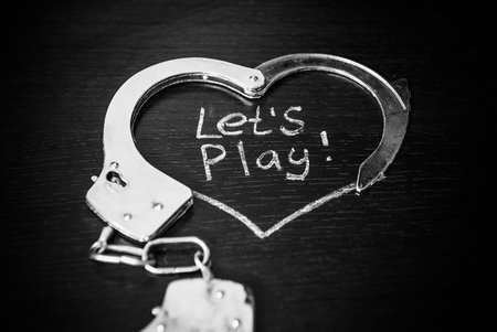 Lets play bdsm. Handcuffs for role-playing games like heart. Handcuffs with caption on black background.