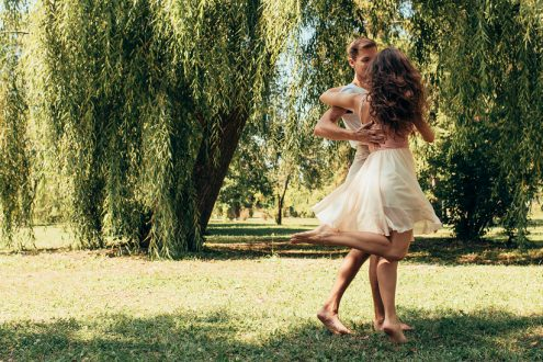Horizontal outdoor image of romantic couple in love dating outdoors at the park on a sunny day. Happy couple in love dancing together. Date day. Valentine day
