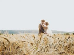 Wedding couple in wheat field in sunlight. Romantic feelings at sunset. Couple in love