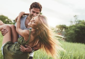 Shot of young woman being carried by her boyfriend in grass field. Couple having fun on their summer holiday.
